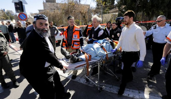 Israeli medics and a policeman evacuate an injured person from the scene of an attack in Jerusalem March 6, 2015. A Palestinian motorist rammed his vehicle into a group of pedestrians standing near a Jerusalem tram stop on Friday, injuring at least five people, Israeli police said. The incident, which police said they were treating as a terrorist attack, took place on a main road in East Jerusalem, the predominantly Arab side of the city, close to an Israeli border police station. REUTERS/Ammar Awad (JERUSALEM - Tags: CIVIL UNREST POLITICS TPX IMAGES OF THE DAY)