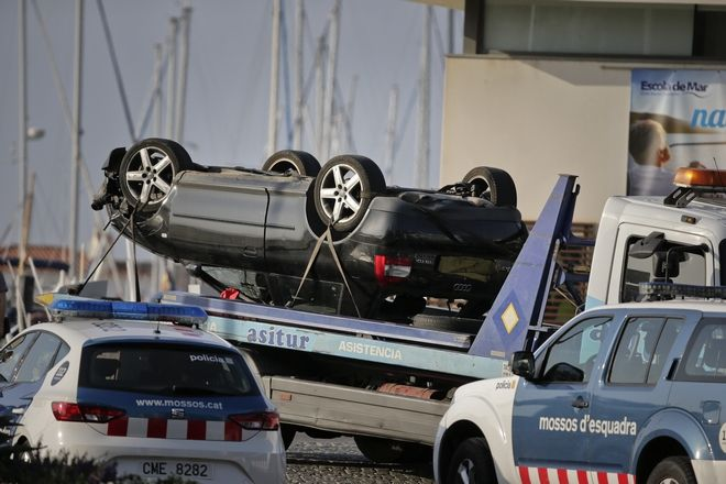 An overturned car is transported on a platform from the spot where terrorists were intercepted by police in Cambrils, Spain, Friday, Aug. 18, 2017. The police force for Spain's Catalonia region says the five suspects shot and killed in the resort town of Cambrils were carrying bomb belts, which have been detonated by the force's bomb squad. (AP Photo/Emilio Morenatti)