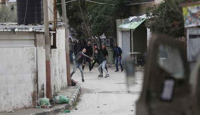 Palestinians clash with Israeli troops in the West Bank city of Jenin, Thursday, Jan. 18, 2018. Israeli police say special forces killed a Palestinian gunman in the West Bank who allegedly killed an Israeli in a drive-by shooting earlier this month. (AP Photo/Majdi Mohammed)