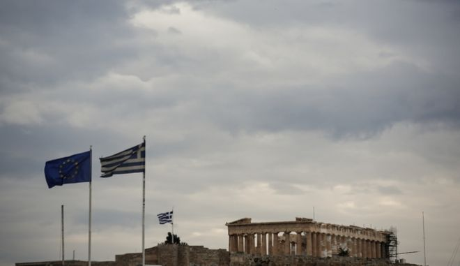 A EU and a Greek flag flutter in front of the temple of the Parthenon in Athens, Sunday, May 22, 2016. Greek parliament votes on a bill ahead of a Eurogroup meeting next week which is likely to unlock bailout funds for the country. (AP Photo/ Yorgos Karahalis )