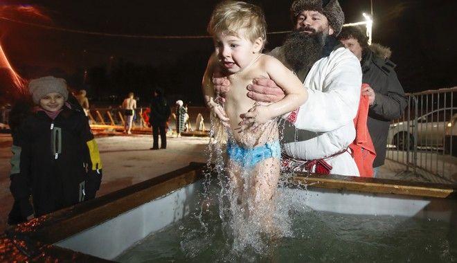 Άνδρας βουτά μικρό παιδιί στο νερό ενώ επικρατούν πολικές θερμοκρασίες, ανήμερα των Θεοφανίων στην Αγ. Πετρούπολη