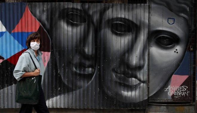 Γυναίκα με μάσκα περνάει μπροστά από γκράφιτι στο κέντρο της Αθήνας