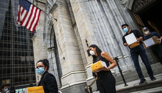 Συγγενείς θυμάτων του κορονοϊού με τις στάχτες των αγαπημένων τους προσώπων ανά χείρας στη Νέα Υόρκη