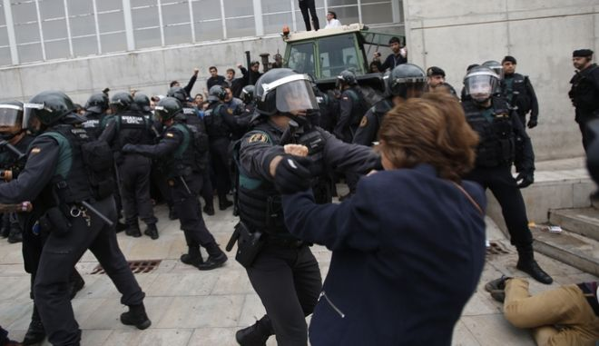Civil guards clear people away from the entrance of a sports center, assigned to be a polling station by the Catalan government in Sant Julia de Ramis, near Girona, Spain, Sunday, Oct. 1, 2017. Scuffles have erupted as voters protested as dozens of anti-rioting police broke into a polling station where the regional leader was expected to show up for voting on Sunday. (AP Photo/Francisco Seco)