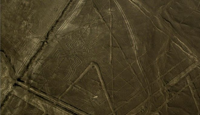 """In this photo taken Oct. 18, 2009 from the air, a figure known as """"the spider"""" is seen, centre left in the zone known as the Nazca lines in the coastal Nazca Desert where, centuries ago, indigenous groups etched mysterious figures in the sand that today are a UNESCO World Heritage Site. A small plane carrying tourists crashed Thursday Feb. 25, 2010 near the famed ancient geoglyphs killing all seven people on board. The Cessna 206 was carrying three Chileans and four Peruvians, local airport chief Enrique Gamboa said. The aircraft crashed about 150 yards (meters) from """"the spider"""" but did not damage it, said Americo Baiocchi, director of the Nazca National Cultural Institute.The glyphs are only fully recognizable from the air, and overflights are popular with travelers. (AP Photo/Harold Heckle)"""