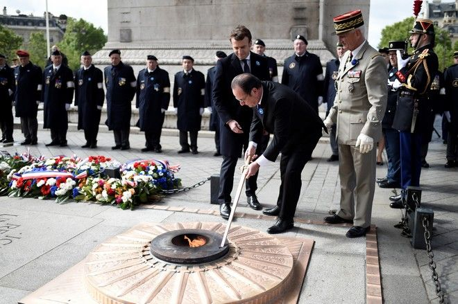 French President-elect Emmanuel Macron, center behind, watches outgoing President Francois Hollande lighting up the Tomb of the Unknown soldier during a ceremony to mark the end of World War II at the Arc de Triomphe in Paris, Monday, May 8, 2017. France's youngest president faces the daunting task of reuniting a troubled and divided nation riven by anxieties about terrorism and chronic unemployment and ravaged by a bitter campaign against defeated populist Marine Le Pen. (Stephane de Sakutin, Pool via AP)