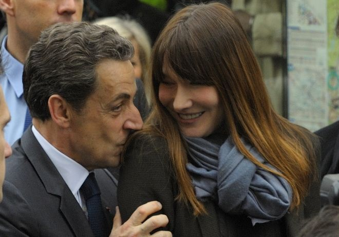 French President and UMP candidate Nicolas Sarkozy kisses his wife Carla Bruni-Sarkozy as they are greeted by supporters after casting their votes in the second round of French presidential elections in Paris, France, Sunday, May 6, 2012. (AP Photo/Philippe Wojazer , POOL)