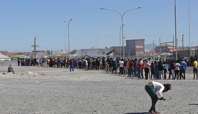 Κάτοικοι της παραγκούπολης Καϊέλιτσα στέκονται στη σειτά για τρόφιμα.