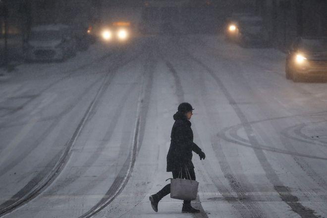 Γυναίκα διασχίζει το δρόμο μέσα στο χιονιά