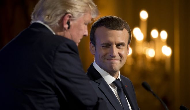 French President Emmanuel Macron winks at President Donald Trump during a joint news conference at the Elysee Palace in Paris, Thursday, July 13, 2017. (AP Photo/Carolyn Kaster)