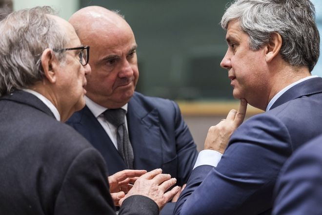 Portugal's Finance Minister Mario Centeno, right, talks with Spain's Economy Minister Luis de Guindos, center, and Italy's Finance Minister Pier Carlo Padoan during a meeting of eurozone finance ministers at the Europa building in Brussels on Monday, Dec. 4, 2017. Eurozone finance ministers meet Monday to elect a new president for the club of 19 nations that share the euro currency. (AP Photo/Geert Vanden Wijngaert)