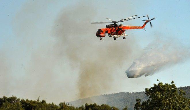 Πυροσβεστικό ελικόπτερο επιχειρεί για την κατάσβεση της πυρκαγιάς σε δασική έκταση στα Βίλια, στην περιοχή Προφήτης Ηλίας τοπ Σάββατο 13 Ιουνίου 2015. Στο έργο της κατάσβεσης συμμετέχουν 25 πυροσβέστες με 11 οχήματα, 2 ομάδες πεζοπόρο τμήμα και από αέρος 1 ελικόπτερο και τέσσερα αεροσκάφη.  (EUROKINISSI/ΑΝΤΩΝΗΣ ΝΙΚΟΛΟΠΟΥΛΟΣ)