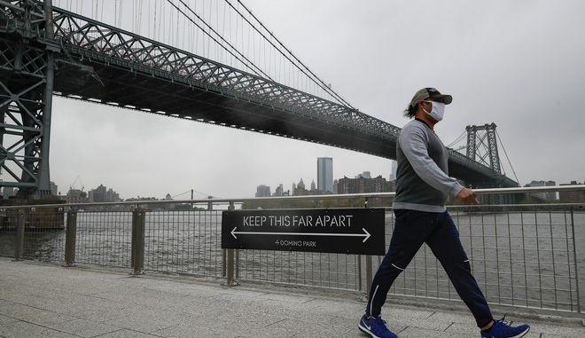 Πολίτης των ΗΠΑ με μάσκα, μπροστά από ένδειξη για μέτρα απόστασης