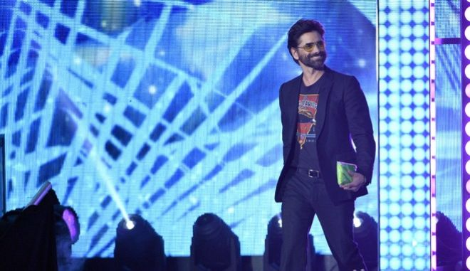John Stamos walks on stage to present the award for favorite villain at the Kids' Choice Awards at the Galen Center on Saturday, March 11, 2017, in Los Angeles. (Photo by Chris Pizzello/Invision/AP)