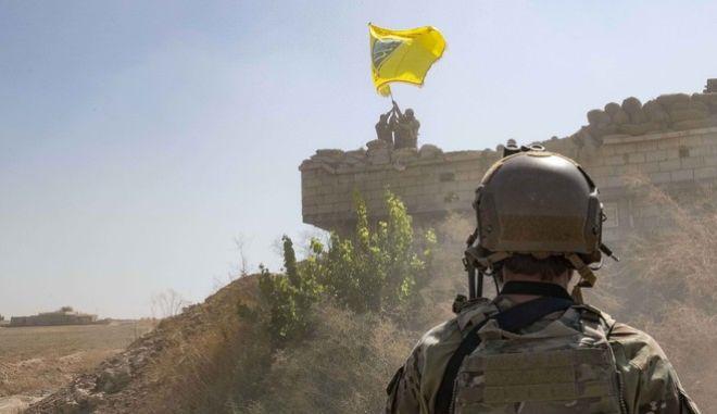 Αμερικανός στρατιώτης και πίσω Κούρδοι μαχητές του SDP