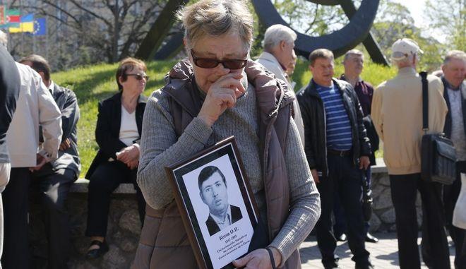 Μια γυναίκα στην Ουκρανία κρατά τη φωτογραφία του συζύγου της που πέθανε μετά την έκρηξη στο Τσέρνομπιλ