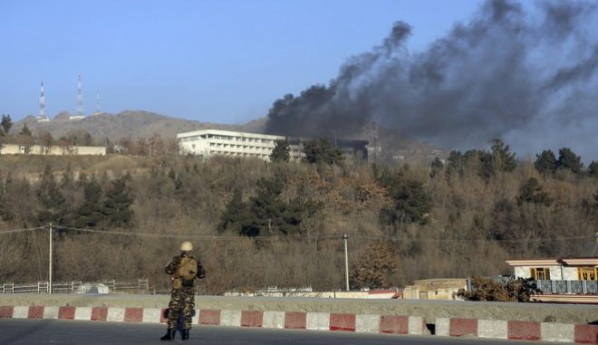 An Afghan security official stand guard as black smoke rises from the Intercontinental Hotel after an attack in Kabul, Afghanistan, Sunday, Jan. 21, 2018. Gunmen stormed the hotel and sett off a 12-hour gun battle with security forces that continued into Sunday morning, as frantic guests tried to escape from fourth and fifth-floor windows. (AP Photo/Rahmat Gul)