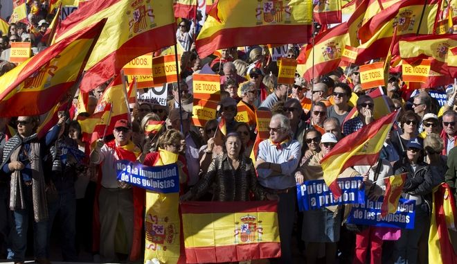 People wave Spanish flags during a mass protest by people angry with Catalonia's declaration of independence, in Madrid, Spain, Saturday, Oct. 28, 2017. Opponents of independence for Catalonia held the rally in the Spanish capital as thousands of people turned out in the Plaza de Colon. The rally comes after one of the country's most tumultuous days in decades. Signs read ' No to the impunity of the Coup Ieaders' and 'Puigemont to Prison'. (AP Photo/Paul White)