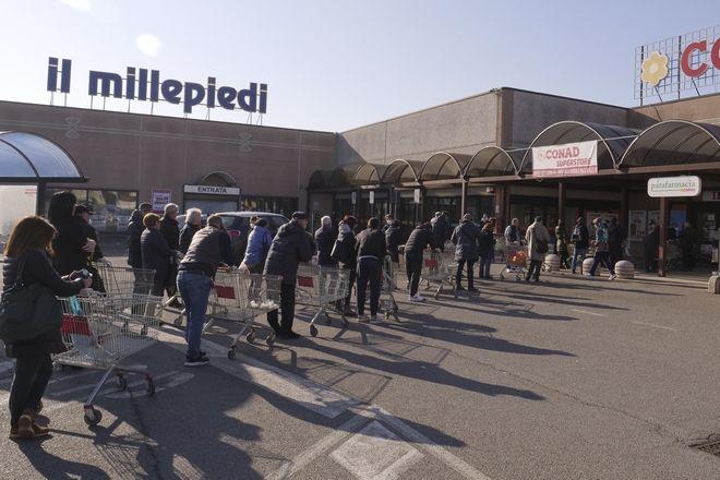 Άνθρωποι περιμένουν έξω από σούπερ μάρκετ στο Casalpusterlengo της Βόρειας Ιταλίας, τη Δευτέρα, 24 Φεβρουαρίου 2020