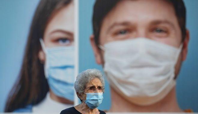Γυναίκα με μάσκα περπατά μπροστά από αφίσες για τον κορονοϊό