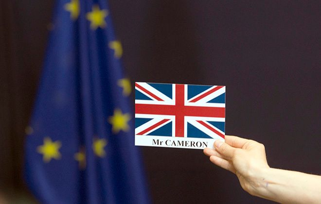 A member of the press service holds up a placement card for British Prime Minister David Cameron at the end of a group photo at an EU summit in Brussels on Tuesday, June 28, 2016. EU heads of state and government meet Tuesday and Wednesday in Brussels for the first time since Britain voted to leave the European Union, throwing British and European politics into disarray. (AP Photo/Geoffroy Van der Hasselt)