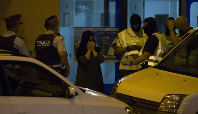Police block the entrance of a telephone call centre as they search the premises in Ripoll, Spain, Tuesday Aug. 22, 2017. Police in Catalonia said that agents are searching Tuesday a house and a cybercafe in two different northeastern Spanish towns in connection to the deadly attacks last week that killed 15 people in and near Barcelona. (AP Photo/Francisco Seco)