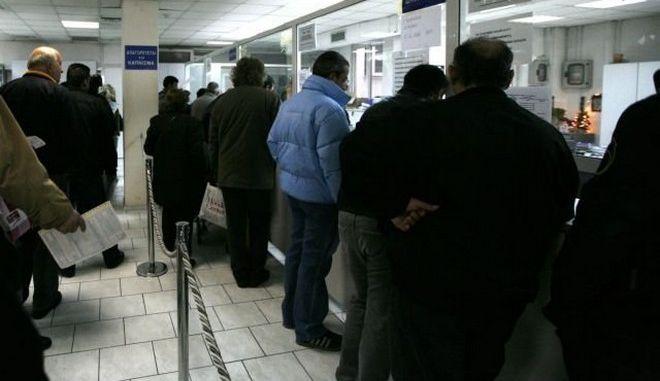 Πολίτες περιμένουν στην ουρά σε εφορία στο κέντρο της Αθήνας