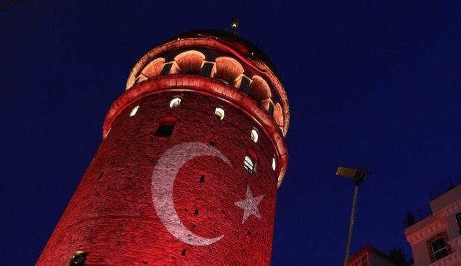 People take photos with their phones at the iconic Galata Tower, illuminated in Turkish flag colors, in Istanbul, Saturday, July 30, 2016. Dozens of staff at Turkey's highest court have been suspended from their jobs as part of the crackdown in the wake of a failed military coup, authorities said. (AP Photo/Petros Karadjias)