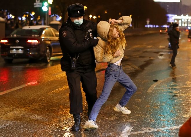 Riot police detain a young woman during a protest against the jailing of opposition leader Alexei Navalny in Pushkin square in Moscow, Russia, Saturday, Jan. 23, 2021. Russian police arrested more than 3,400 people Saturday in nationwide protests demanding the release of opposition leader Alexei Navalny, the Kremlin's most prominent foe, according to a group that counts political detentions. In Moscow, an estimated 15,000 demonstrators gathered in and around Pushkin Square in the city center, where clashes with police broke out and demonstrators were roughly dragged off by helmeted riot officers to police buses and detention trucks. Some were beaten with batons. (AP Photo/Alexander Zemlianichenko)