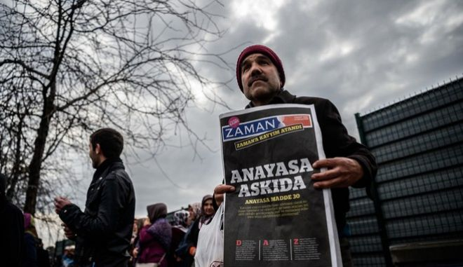 A Zaman supporter holds the latest edition of Turkish daily newspaper Zaman with the headline 'Suspended the constitution' in front of the newspaper's headquarters in Istanbul on March 5, 2016, after Turkish authorities seized the headquarters in a midnight raid.  Turkish authorities on March 5 were in control of the newspaper staunchly opposed to President Recep Tayyip Erdogan after using tear gas and water cannon to seize its headquarters in a dramatic raid that raised fresh alarm over declining media freedoms. Police fired the tear gas and water cannon just before midnight at a hundreds-strong crowd that had formed outside the headquarters of the Zaman daily in Istanbul following a court order issued earlier in the day. / AFP / OZAN KOSE        (Photo credit should read OZAN KOSE/AFP/Getty Images)