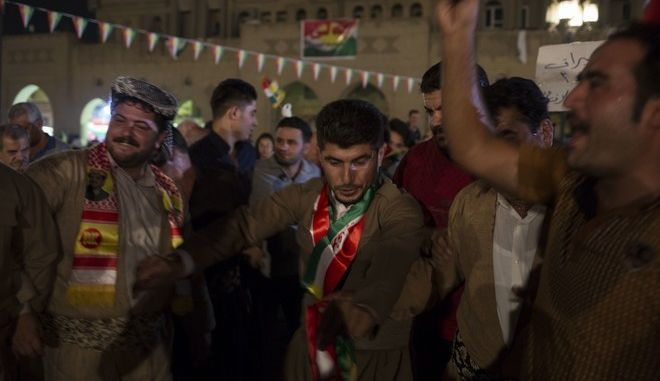 Kurdish men dance in the streets of Irbil after polling stations closed on Monday, Sept. 25, 2017. The Kurds of Iraq were voting in a referendum on support for independence that has stirred fears of instability across the region, as the war against the Islamic State group winds down. (AP Photo/Bram Janssen)