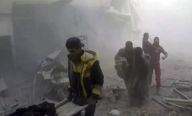 This frame grab from video released on Saturday, Feb 24, 2018 by the Syrian Civil Defense group known as the White Helmets, shows members of the Syrian Civil Defense group help residents during airstrikes and shelling by Syrian government forces, in Ghouta, a suburb of Damascus, Syria. A new wave of airstrikes and shelling on eastern suburbs of the Syrian capital Damascus left at least 22 people dead and more than a dozen wounded Saturday, raising the death toll of a week of bombing in the area to nearly 500, including scores of women and children. (Syrian Civil Defense White Helmets via AP)