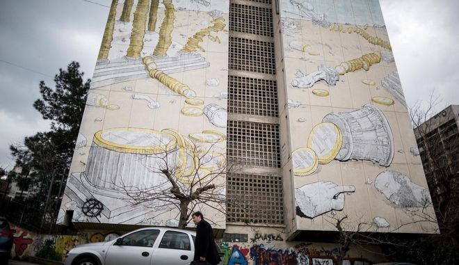 A man makes his way in front of a mural depicting the Greek economy crisis covers a building housing student residences, in Thessaloniki, Greece on March 13, 2015. /                ,  ,   13 , 2015.
