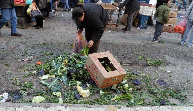 Στιγμιότυπο από την λαϊκή αγορά του Νέου Κόσμου το Σάββατο 3 Ιανουαρίου 2015, όπου γυναίκα μαζεύει τα υπολλείματα αγροτικών προιόντων που έχουν αφήσει οι παραγωγοί στο δρόμο. (EUROKINISSI/ΓΙΩΡΓΟΣ ΚΟΝΤΑΡΙΝΗΣ)