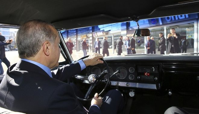 Turkey's President Recep Tayyip Erdogan is surrounded by his security members as he drives a classic car in Ankara, Turkey, Friday, Dec. 2, 2016. Turkish Prime Minister Binali Yildirim has met Thursday with Devlet Bahceli, the leader of the opposition Nationalist Movement Party, to discuss plans for constitutional reforms that would usher in a presidential system expanding Erdogan's powers.(Kayhan Ozer, Presidential Press Service, Pool photo via AP)