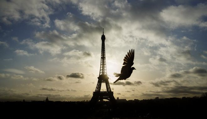 FILE - In this Nov. 15, 2015 file photo, a bird flies while the Eiffel Tower, which remained closed on the first of three days of national mourning after terror attacks, is seen in the background in Paris. Between terror attacks, Zika and mass shootings, there's lots of bad news about popular destinations around the world. Where does that leave travelers who may want to stay home instead of going through with a trip? It depends on the circumstances. Cancel-for-any-reason insurance is expensive to buy but provides refunds if you change your mind about a trip. Standard trip insurance may also cover cancellations to a destination hit by terrorism for a period of days following an attack. (AP Photo/Daniel Ochoa de Olza, File)