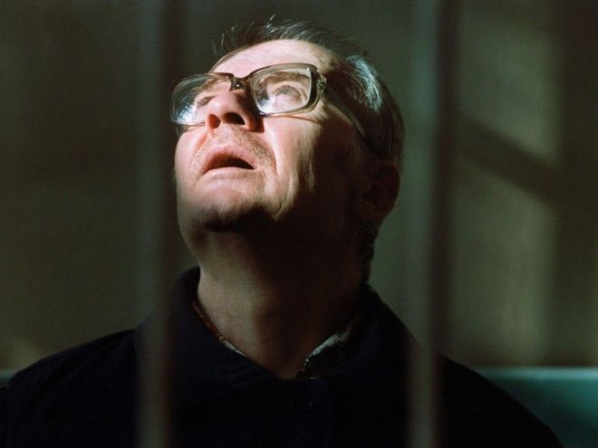 Chikatilo, also known as 'Rostov Ripper', looks at the sun coming through window while waiting for the judge to read the 300 pages verdict in Rostov-on-Don, Russia October 15, 1992 . A People's Court sentenced the 'Rostov Ripper' to death by shooting for 52 sex-and-torture murders during a 12-year rampage through southern Russia, Ukraine and Uzbekistan REUTERS/Grigory Dukor HIGHEST QUALITY AVIALBLE - RTR19MT4