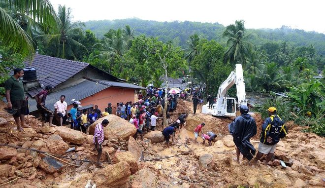 Sri Lankans watch military rescue efforts at the site of a landslide at Bellana village in Kalutara district, Sri Lanka, Friday, May 26, 2017. Mudslides and floods triggered by heavy rains in Sri Lanka killed dozens and left many more missing on Friday. (AP Photo/Eranga Jayawardena)