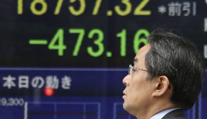 Άνδρας μπροστά από πίνακα χρηματιστηριακών συναλλαγών