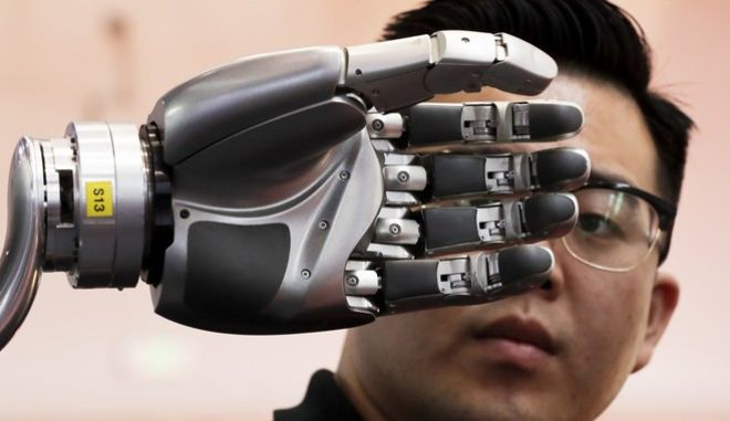 A visitor looks at a robotic hand powered by Kinfinity Glove, developed by the German Aerospace Center, on display at the World Robot Conference at the Yichuang International Conference and Exhibition Centre in Beijing, Wednesday, Aug. 23, 2017. The annual conference is a showcase of China's burgeoning robot industry ranging from companion robots to those deployed on manufacturing assembly line and entertainment. (AP Photo/Andy Wong)