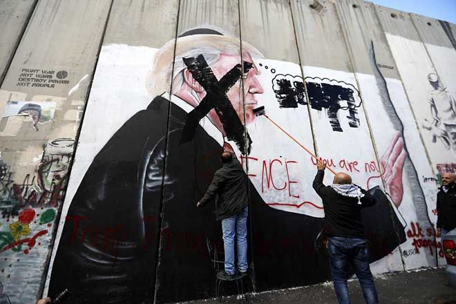 epa06373335 Palestinians paint an 'X' over the face of a picture of US president Donald J. Trump which was painted on the Israeli separation wall in Bethlehem, West Bank, 07 December 2017. Palestinians announced a general strike and a rage day as a protest against US President Donald J. Trump declaration recognizing Jerusalem as the capital of the Israel. On 06 December, US president Donald J. Trump announced that he is recognising Jerusalem as the Israeli capital and will relocate the US embassy from Tel Aviv to Jerusalem.  EPA/ABED AL HASHLAMOUN