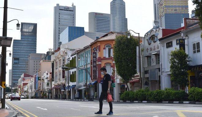 Άνδρας διασχίζει δρόμο της Σιγκαπούρης εν μέσω καραντίνας