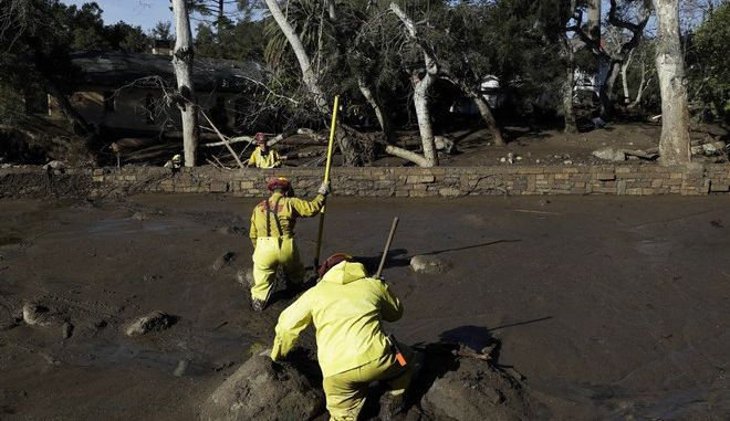 A Cal Fire search and rescue crew walks through mud near homes damaged by storms in Montecito, Calif., Friday, Jan. 12, 2018.  The mudslide, touched off by heavy rain, took many homeowners by surprise early Tuesday, despite warnings issued days in advance that mudslides were possible because recent wildfires had stripped hillsides of vegetation that normally holds soil in place. (AP Photo/Marcio Jose Sanchez)