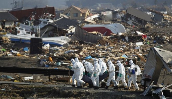 FILE - In this April 15, 2011 file photo,  Japanese police officers carry a body during a search and recovery operation for missing victims in the area devastated by the March 11 earthquake and tsunami in Namie, Fukushima Prefecture, northeastern Japan.  Japan is marking the anniversary of the disaster Saturday, March 11, 2017 with somber ceremonies in Tokyo and in cities and towns in the northeast. Most of the towns devastated in the March 11, 2011 disasters have only partially rebuilt, and local authorities are struggling to finance construction. Meanwhile, despite an abundance of jobs thanks to the rebuilding, the population in most of the region is falling. (AP Photo/Hiro Komae, File)