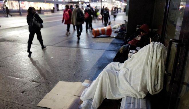 A homeless person sleeps under a blanket while seated on a New York sidewalk, Wednesday, Jan. 11, 2017. (AP Photo/Mark Lennihan)