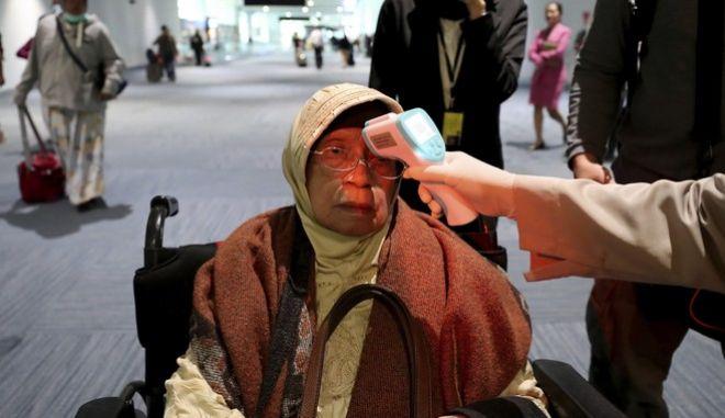 Έλεγχος θερμοκρασίας ταξιδιώτισσας σε αεροδρόμιο, για πρόληψη διάδοσης του ιού.