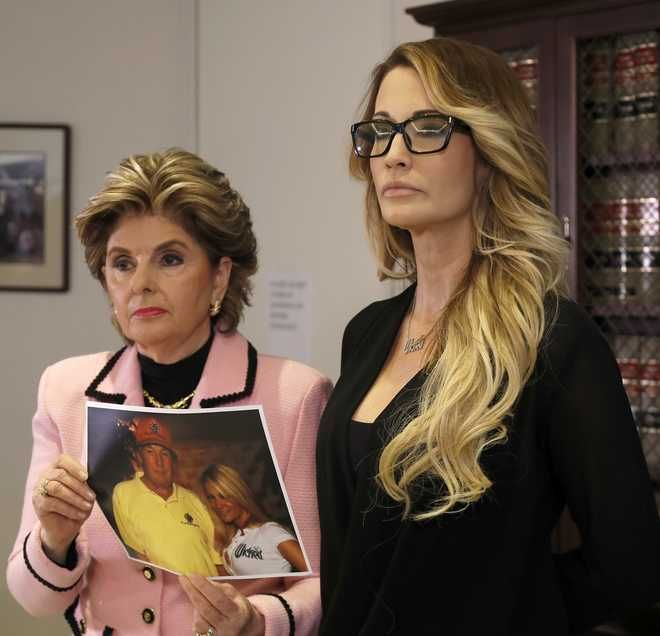 "Jessica Drake stands with her attorney, Gloria Allred, as she holds a photo of Drake and Donald Trump during a news conference in Los Angeles on Saturday, Oct. 22, 2016. Drake, an adult film actress, said Donald Trump kissed her and two other women on the lips ""without asking for permission"" when they met him after a golf tournament in 2006. (AP Photo/Ryan Kang)"