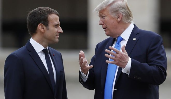 French President Emmanuel Macron listens to U.S. President Donald Trump, right, in the courtyard of les Invalides after a welcoming ceremony in Paris, Thursday, July 13, 2017. Trump and French President Emmanuel Macron are meeting at the Invalides monument for a tour of the golden-domed building housing some of France's greatest war heroes, including Napoleon Bonaparte and the Supreme Allied Commander in World War I. (Yves Herman/ Pool Photo via AP)