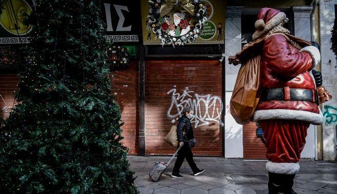 Γυναίκα με μάσκα περνάει μπροστά από Άγιο Βασίλη
