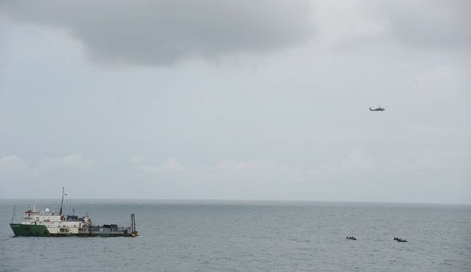 Indonesia's MGS Geosurvey, left, a helicopter and navy divers take part in a search operation for the victims of AirAsia Flight 8501 on the Java Sea, Indonesia, Thursday, Jan. 8, 2015. Divers were hoping to zero in on the flight's black boxes Thursday, after search and recovery operations got a much-needed boost with the discovery of a chunk of the plane's tail - nearly two weeks after it plummeted into the sea, killing everyone onboard. (AP Photo/Adek Berry, Pool)